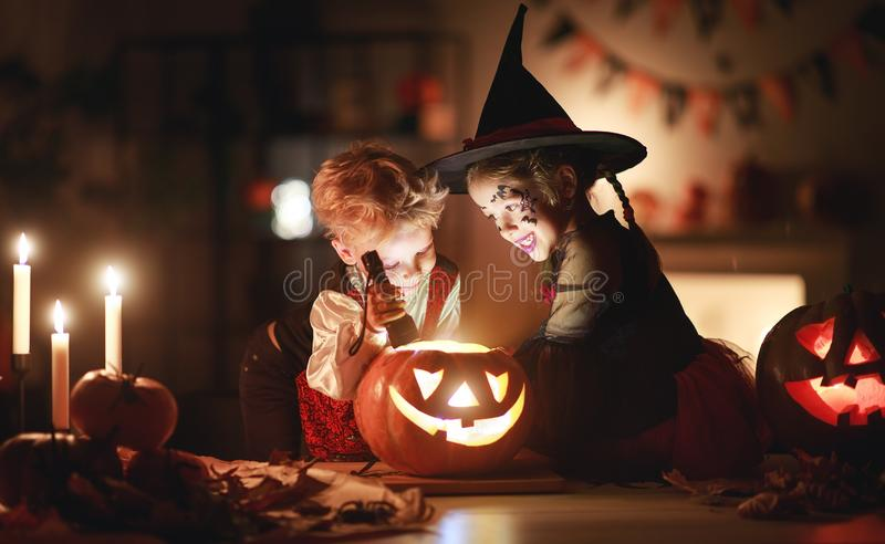 Happy children in costumes of witch and vampire in a dark house in halloween stock photo