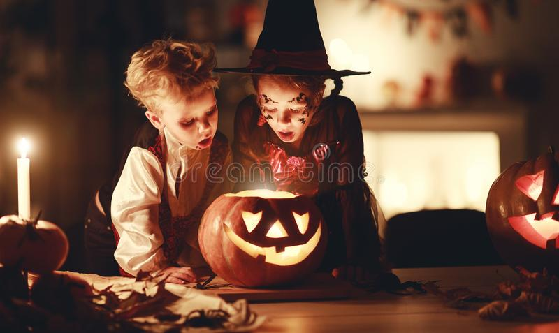 Happy children in costumes of witch and vampire in a dark house in halloween stock photos