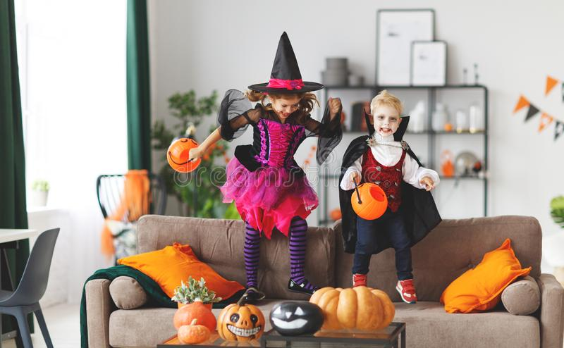 Happy children in costumes of witch and vampire are preparing stock photography