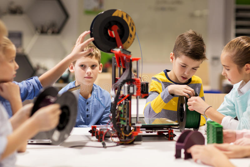 Happy children with 3d printer at robotics school royalty free stock image