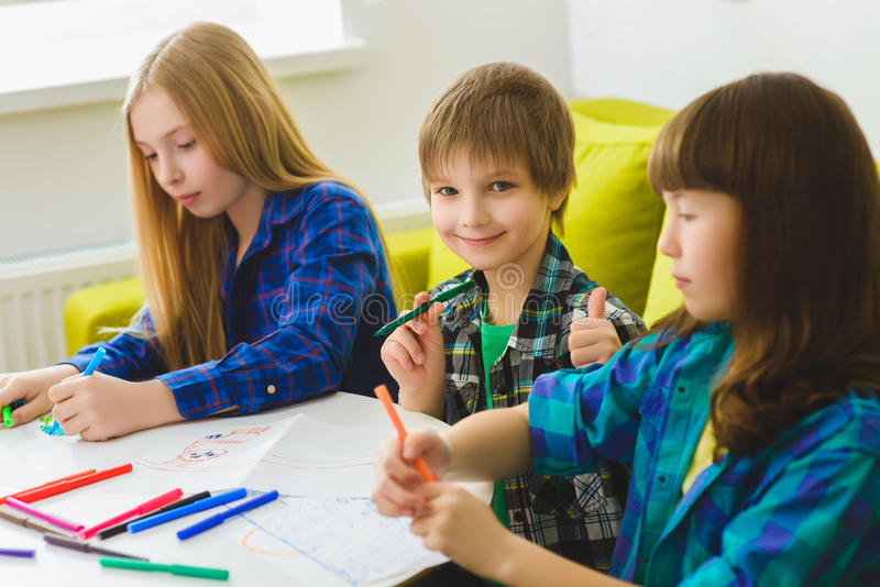 Happy children drawing pictures. Indoor at room. boy showing thumbs up.  stock photo