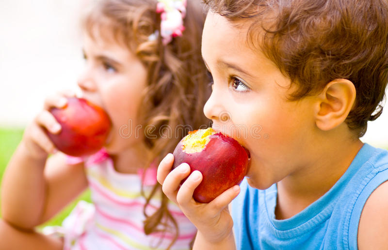 Happy children eating apple. Photo of two happy children eating apples, brother and sister having picnic outdoors, cheerful kids biting red ripe peach, adorable stock photo