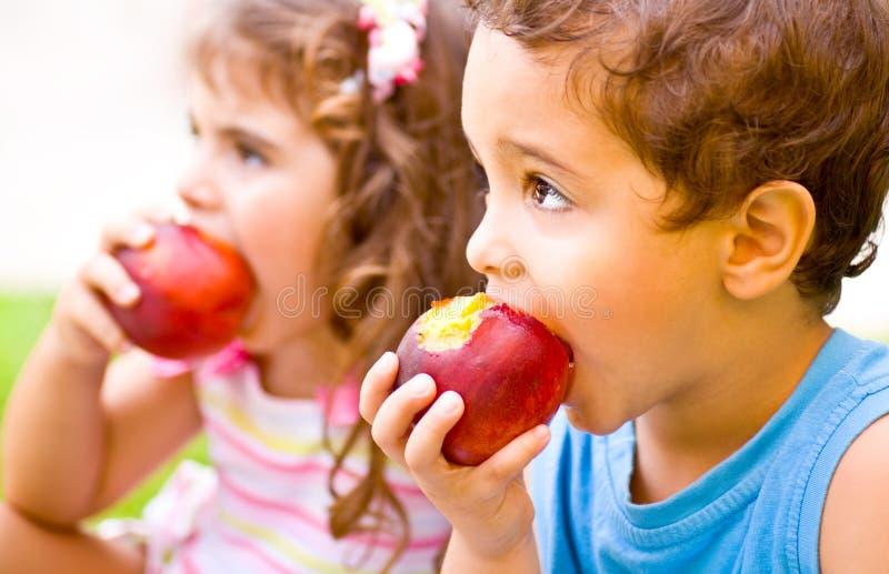 Happy children eating apple stock photo