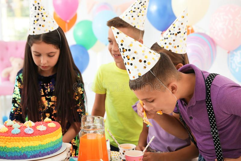 Happy children eating delicious cake at birthday party stock photos