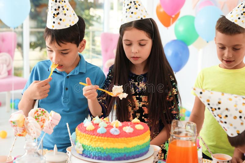 Happy children eating delicious cake at birthday party royalty free stock photos