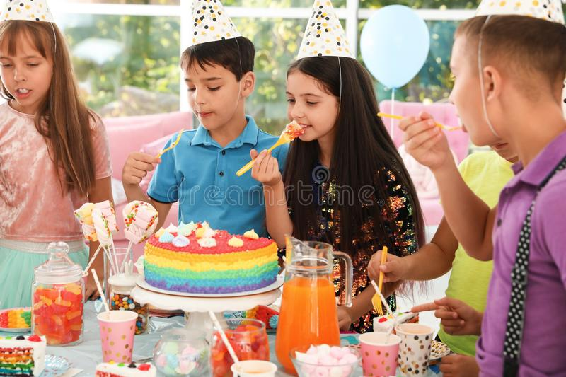 Happy children eating delicious cake at birthday party stock photography