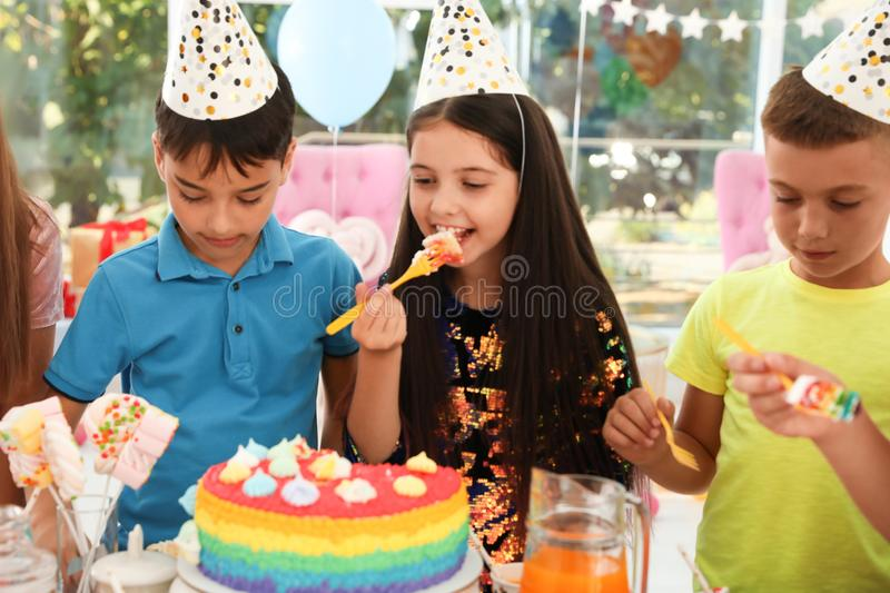 Happy children eating delicious cake at birthday party royalty free stock image