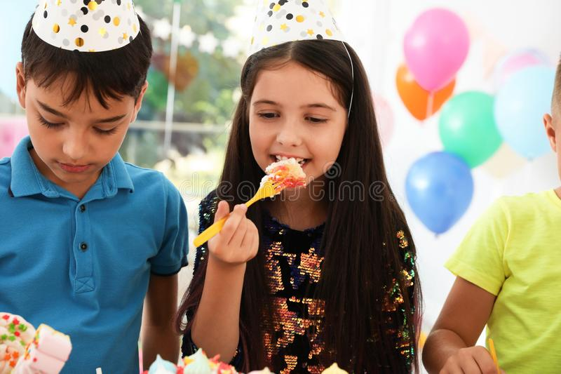 Happy children eating delicious cake at birthday party stock image