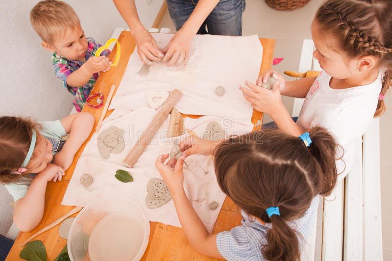 Happy children are engaged with modeling clay. Cute children sculpt something from grey plasticine in kindergarten royalty free stock photo