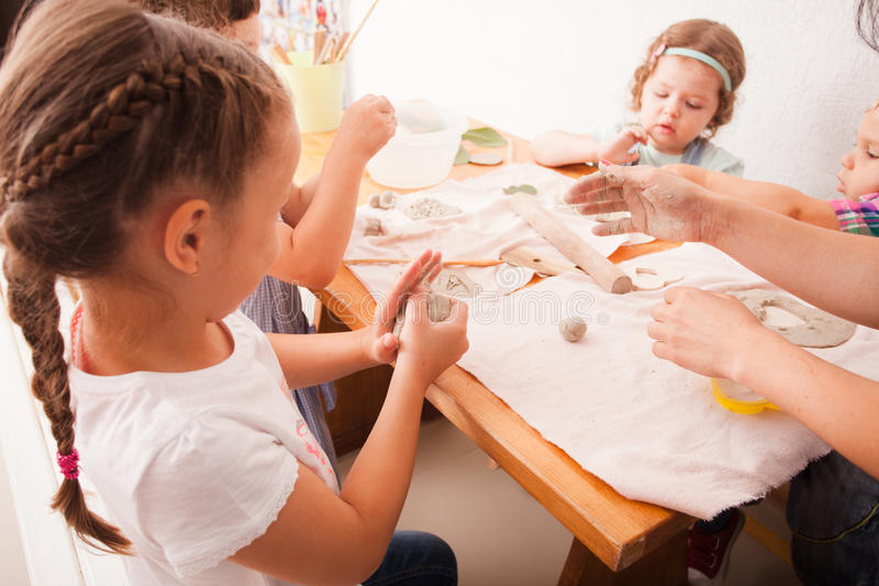 Happy children are engaged with modeling clay. Cute children sculpt something from grey plasticine in kindergarten stock image