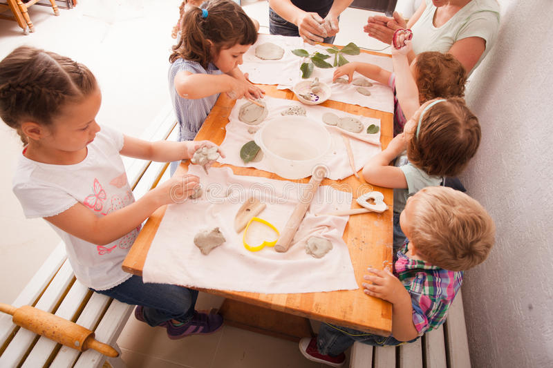 Happy children are engaged with modeling clay. Cute children sculpt something from grey plasticine in kindergarten stock images