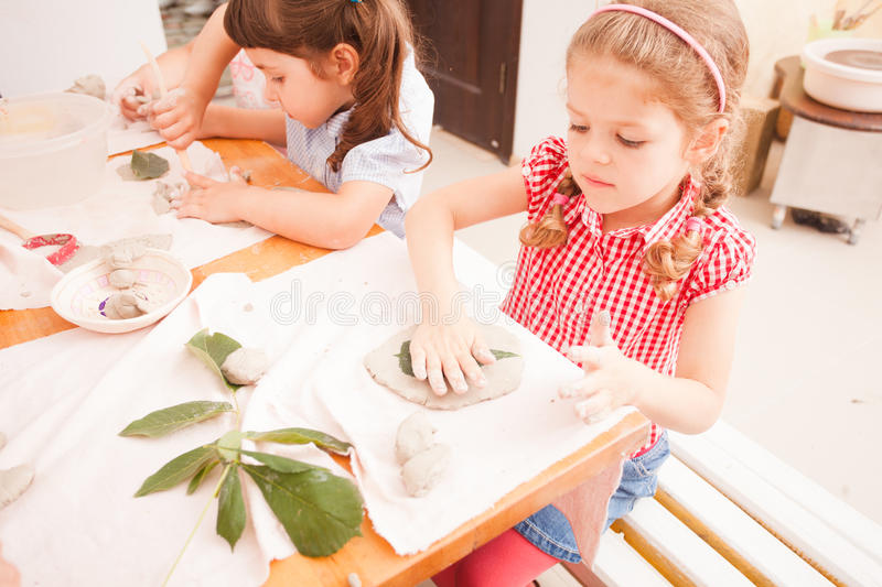 Happy children are engaged with modeling clay. Cute children sculpt something from grey plasticine in kindergarten royalty free stock photos