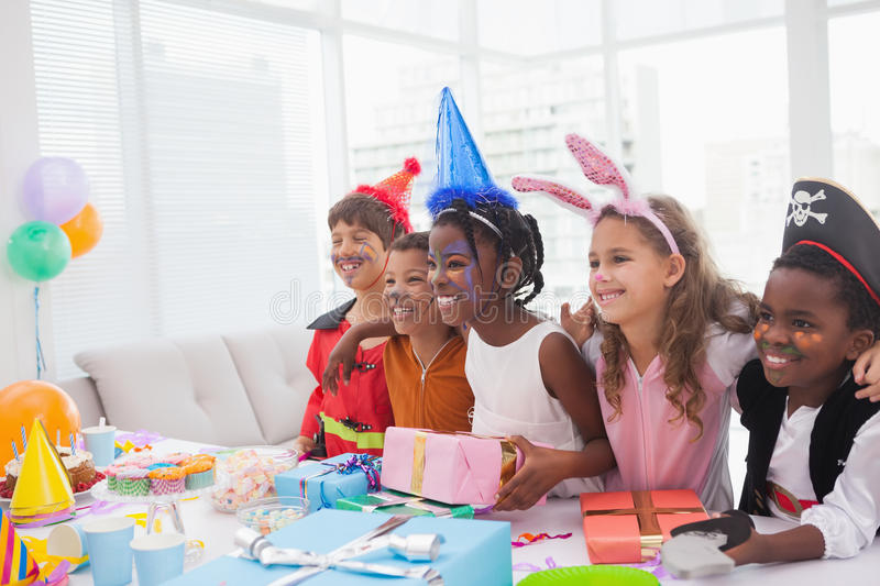 Happy children at fancy dress birthday party. At home in the living room royalty free stock photography