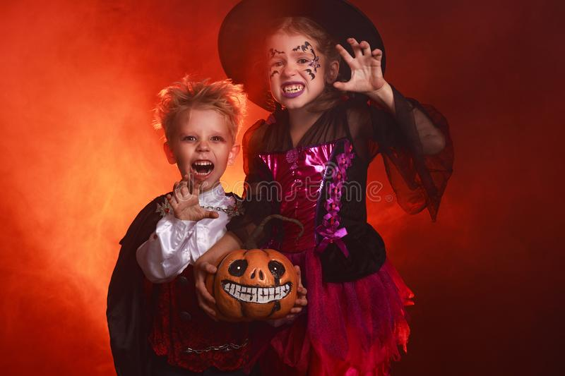 Happy children girl and boy in costumes of witch and vampire in dark red background in halloween royalty free stock images
