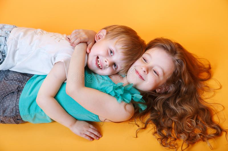 Happy little brother and sister lying on a colored yellow background royalty free stock images