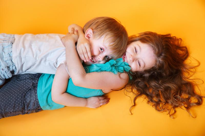 Happy little brother and sister lying on a colored yellow background stock images