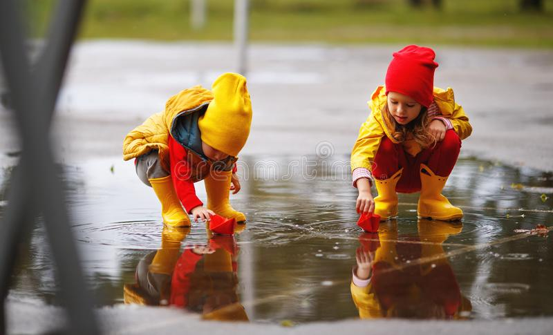 Happy children girl and boy with paper boat in puddle in autumn. Happy children girl and boy with paper boat in a puddle in autumn on nature royalty free stock images