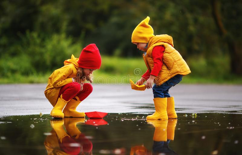 Happy children girl and boy with paper boat in puddle in autumn royalty free stock images