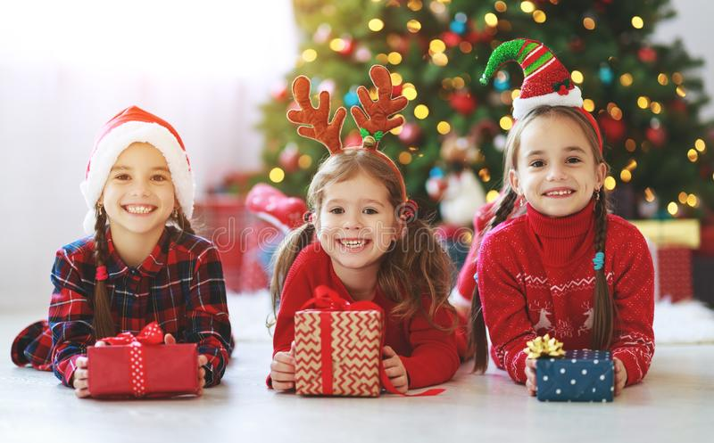 Happy children girls with christmas gifts near tree in morning. Happy children girls with christmas gifts near christmas tree in morning stock images