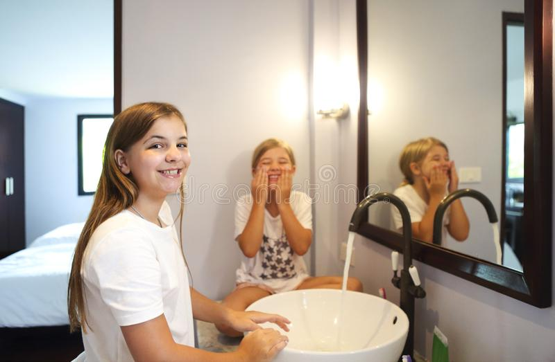Happy children girls are washing their faces in a bathroom royalty free stock photo