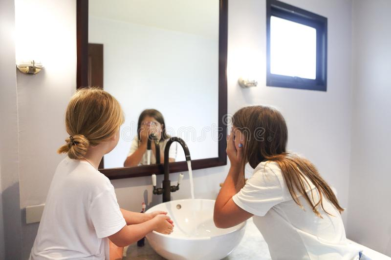 Happy children girls are washing their faces in a bathroom stock images