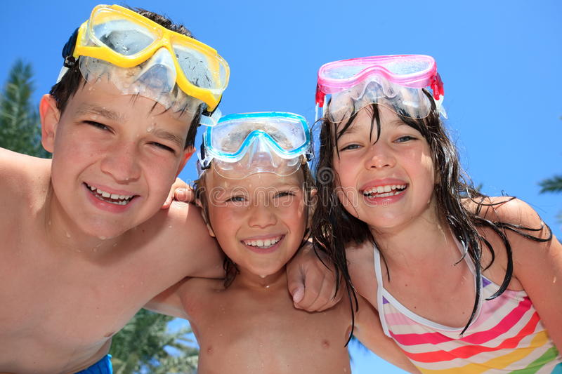 Happy children with goggles. Three happy, smiling children with swimming goggles royalty free stock image