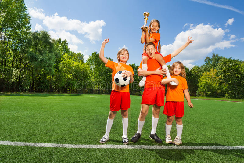 Happy children with golden cup stand in pyramid. Shape together on grass stock photo