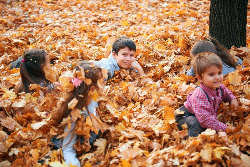 Happy children group playing in heap of yellow leaves, posing, smiling and having fun in autumn city park. Bright yellow trees and royalty free stock photo