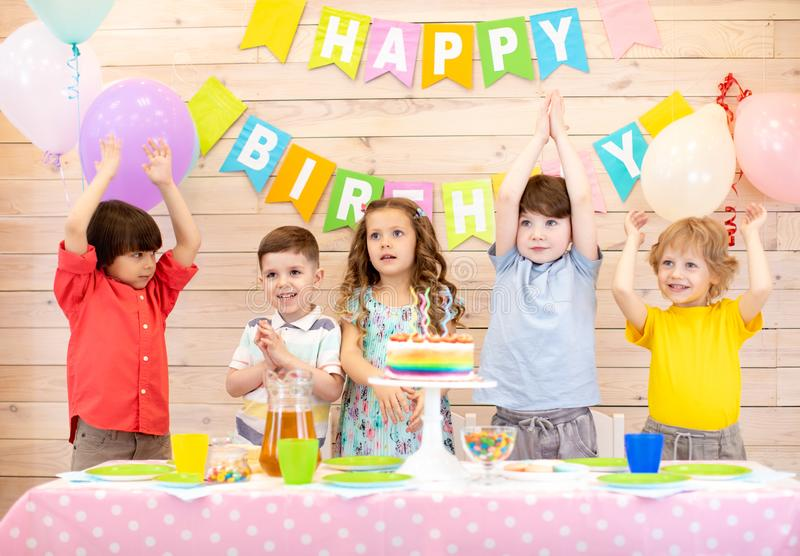 Happy children at table celebrating birthday holiday stock images