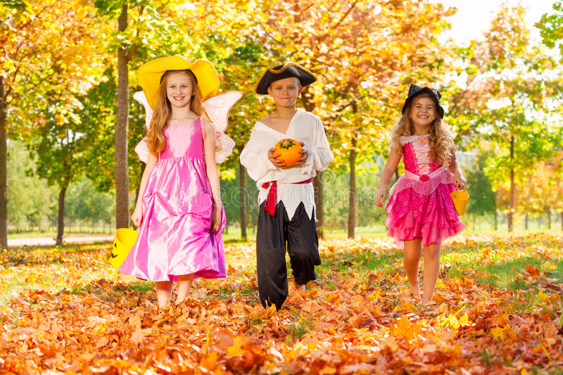 Happy children in Halloween costumes walking. Happy children in Halloween costumes with small pumpkin and buckets in the forest during sunny autumn day time stock image