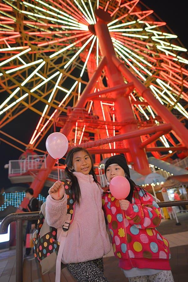 Happy children have fun at Redhorse Osaka. Wheel at night in Osaka, Japan stock photo