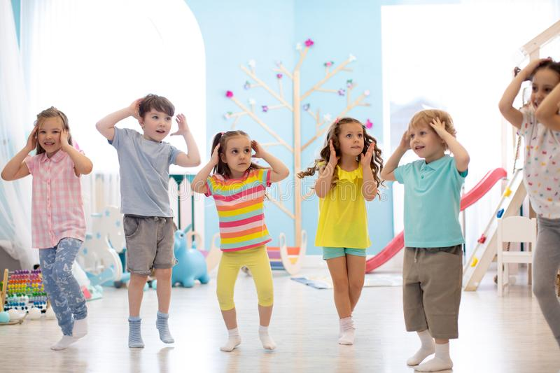 Happy kids having fun dancing indoors in a sunny room at day care or entertainment center stock photo