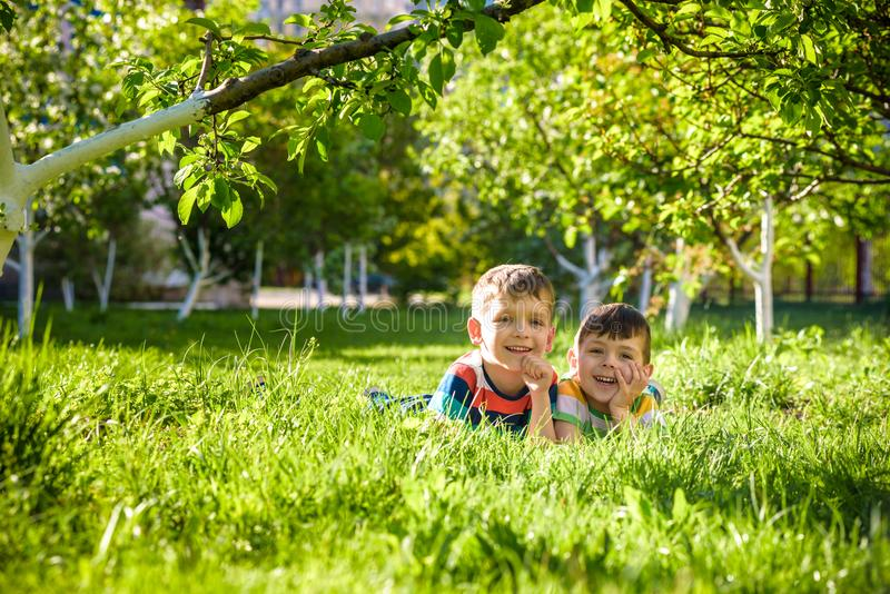 Happy children having fun outdoors. Kids playing in summer park. Little boy and his brother laying on green fresh grass holiday ca stock photography