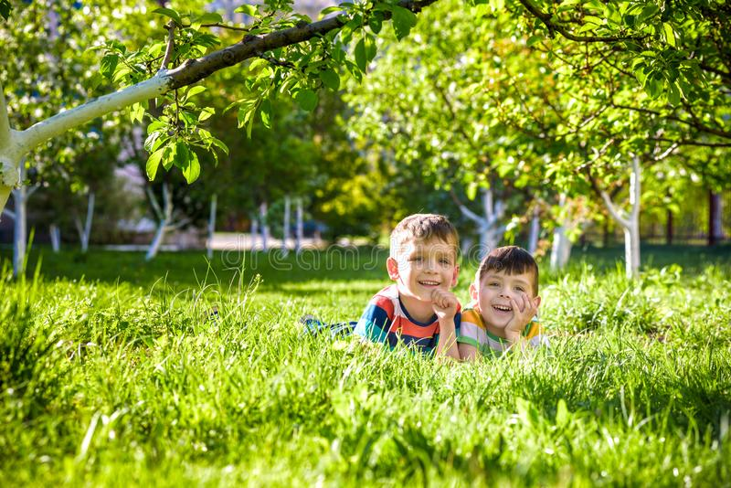 Happy children having fun outdoors. Kids playing in summer park. Little boy and his brother laying on green fresh grass holiday royalty free stock photos