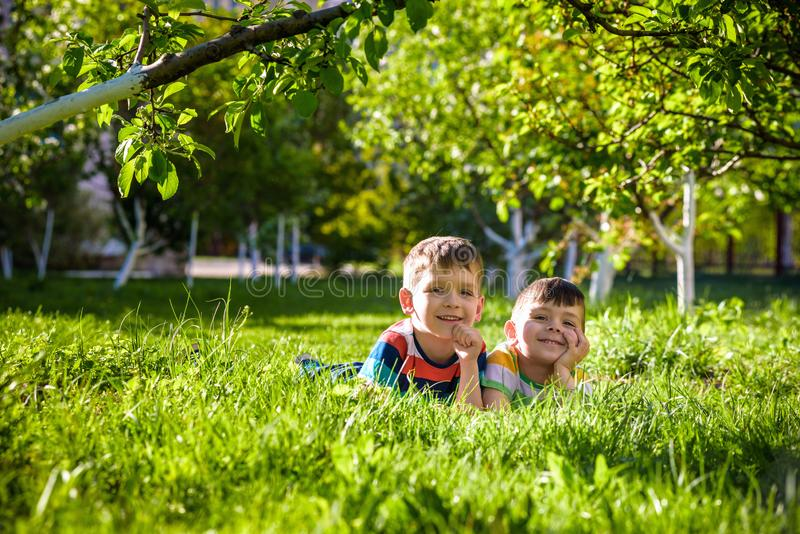 Happy children having fun outdoors. Kids playing in summer park. Little boy and his brother laying on green fresh grass holiday stock photos