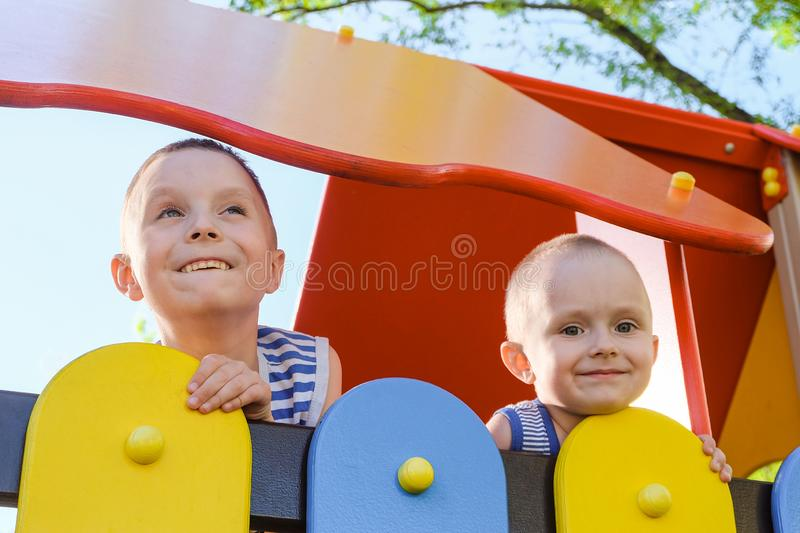Two laughing boys outdoors play at summer time stock photos
