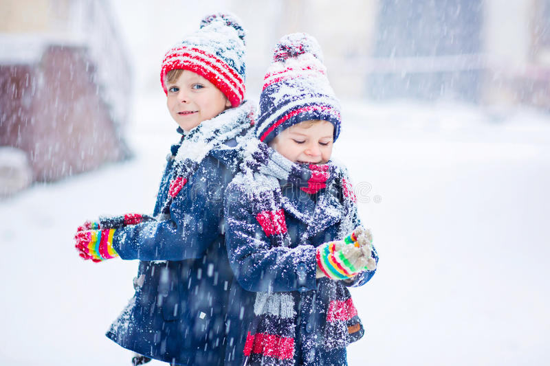 Happy children having fun with snow in winter royalty free stock photography