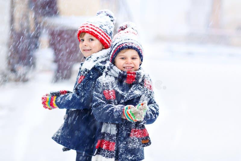 Happy children having fun with snow in winter stock image