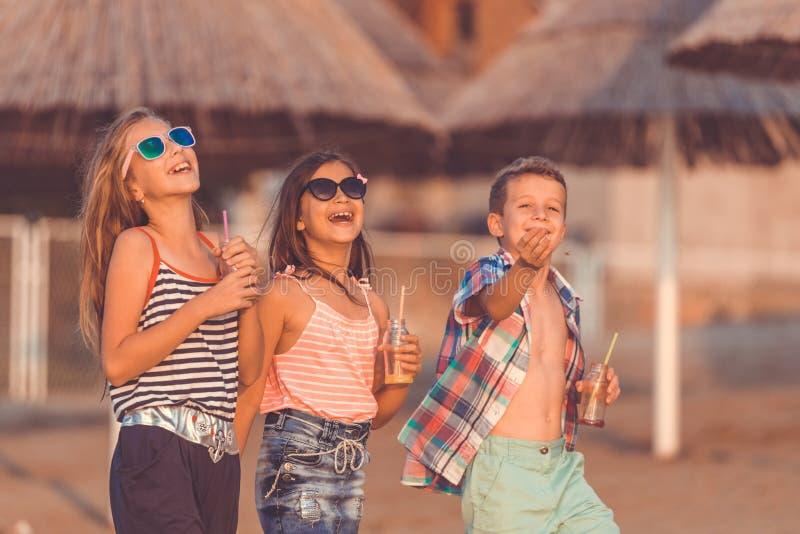 Happy children having fun walking on the beach stock images