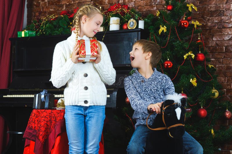 Happy children holding gifts. Waiting for stock photography