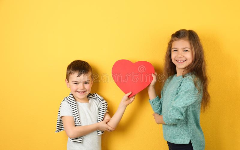 Happy children holding paper heart. On color background royalty free stock photography