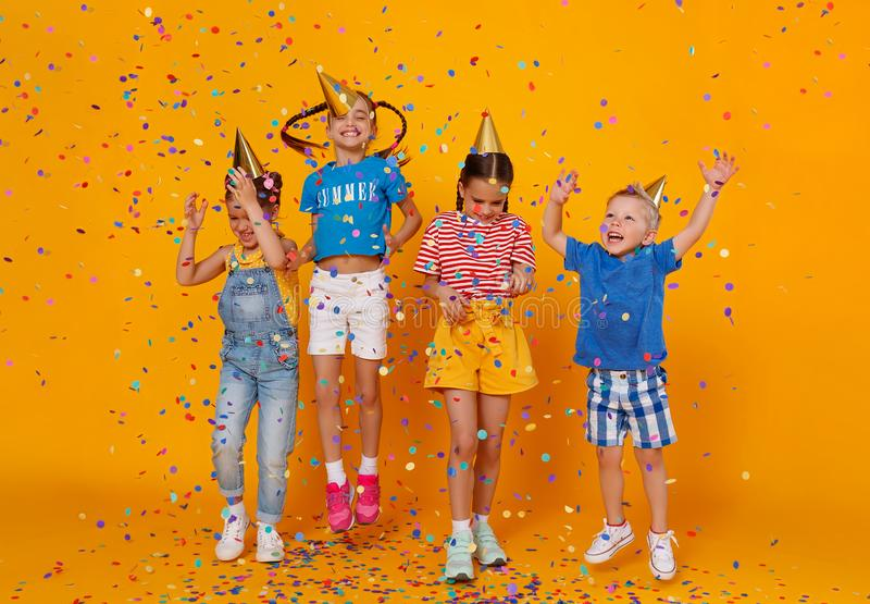 Happy children on holidays  jumping in multicolored confetti on yellow. Happy children on holidays have fun and  jumping in multicolored confetti on yellow stock photo