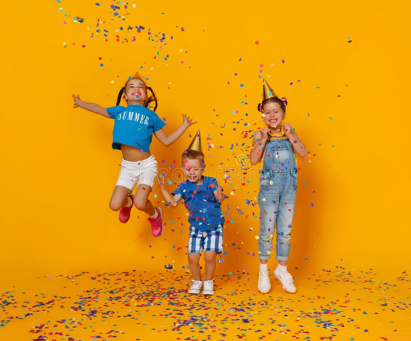 Happy children on holidays  jumping in multicolored confetti on yellow. Happy children on holidays have fun and  jumping in multicolored confetti on yellow royalty free stock photo