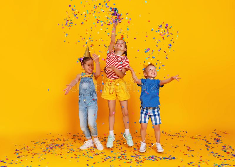 Happy children on holidays  jumping in multicolored confetti on yellow stock image