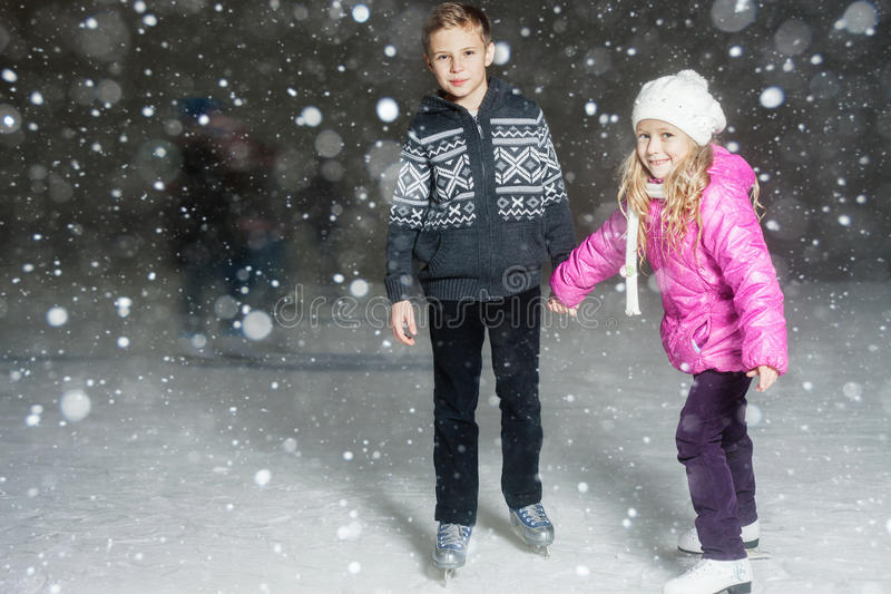 Happy children ice skating at ice rink, winter night. Happy children ice skating at ice rink outdoor, at winter snowy night, sport and healthy lifestyle, ice stock images