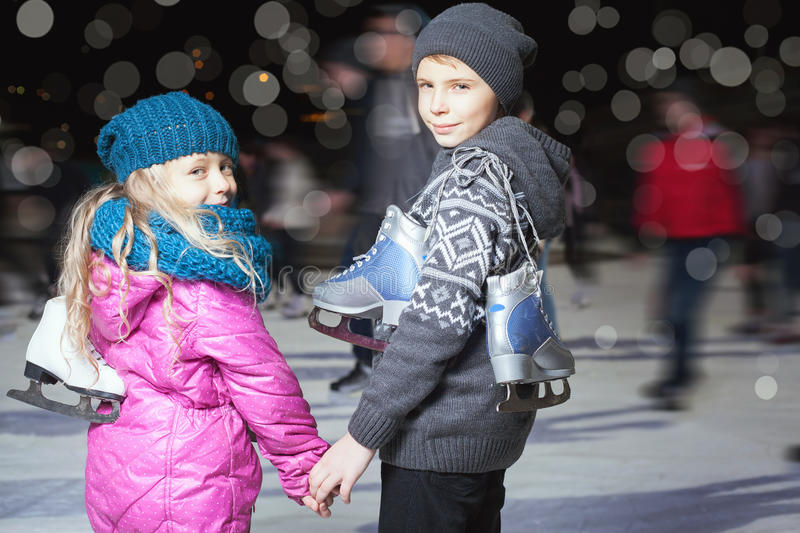 Happy children ice skating at ice rink, winter night. Happy children ice skating at ice rink outdoor, at winter night, sport and healthy lifestyle, ice skating royalty free stock photos