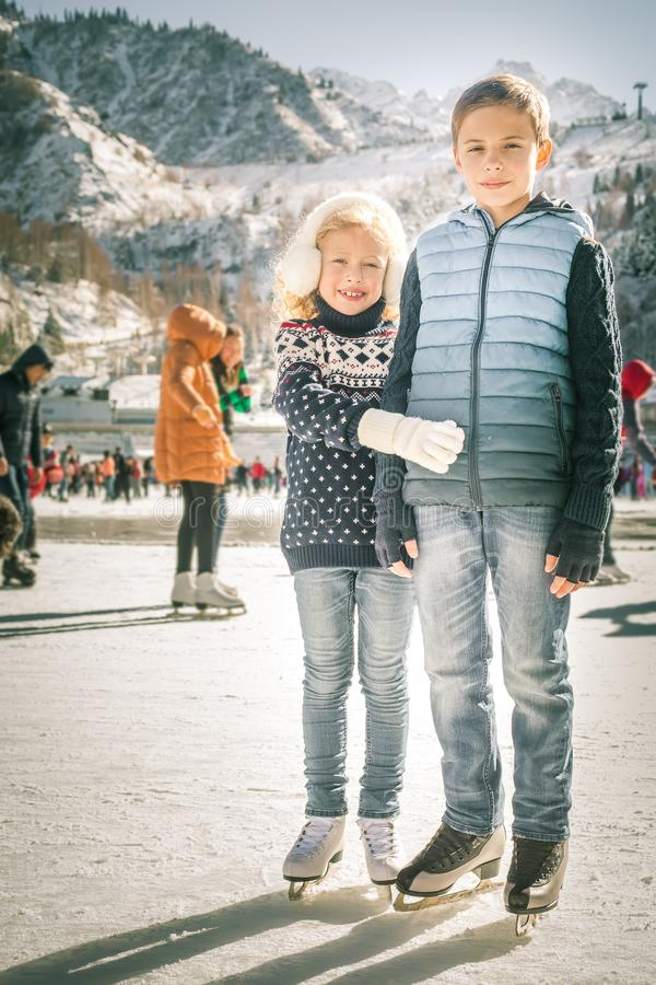 Happy children ice skating at rink outdoor. Happy children ice skating at ice rink outdoor, figure skating, at winter day, sport and healthy lifestyle, ice royalty free stock photo