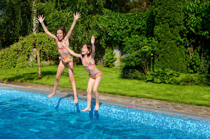 Happy children jump to swimming pool royalty free stock photo