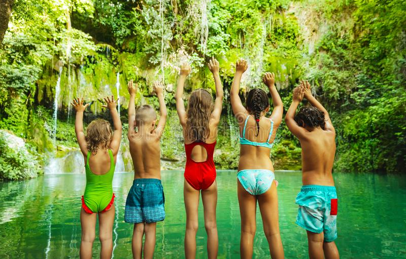 Happy children jumping to the lake stock photo