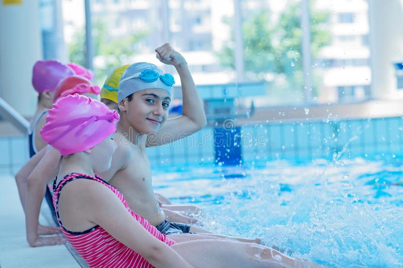 Happy children kids group at swimming pool class learning to swim stock image